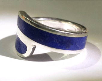 Crossed silver 925 ring filled with pressed finely powdered glass color lapis lazuli.