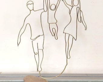 Linear brass sculpture, family represented by a couple with a child.