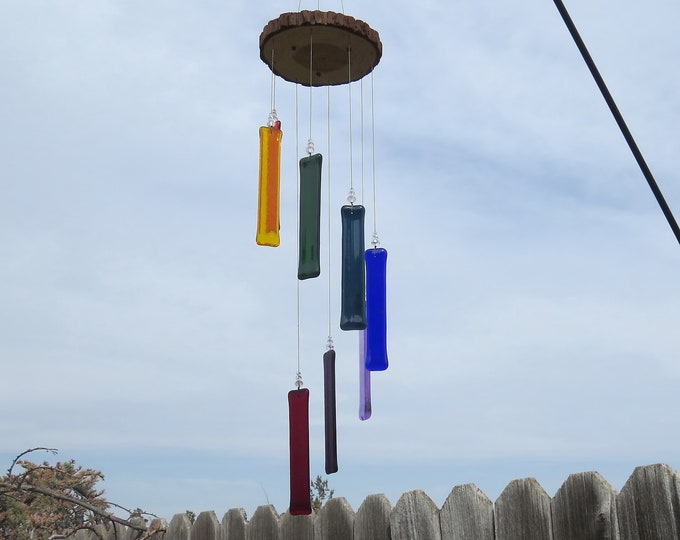 This rainbow glass wind chime hangs from a  wood base and will add that something special to your yard or garden