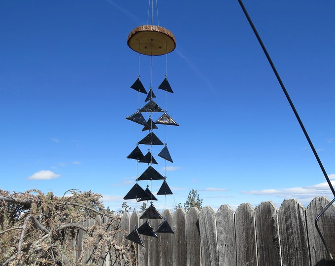 This triangle glass wind chime hangs from a  wood base and will add that something special to your yard or garden