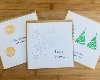 Three handmade Christmas cards featuring papercut foil trees, snow and baubles
