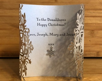 Snowflake charm papercut Christmas card features snowflake charm that can be reused as decoration