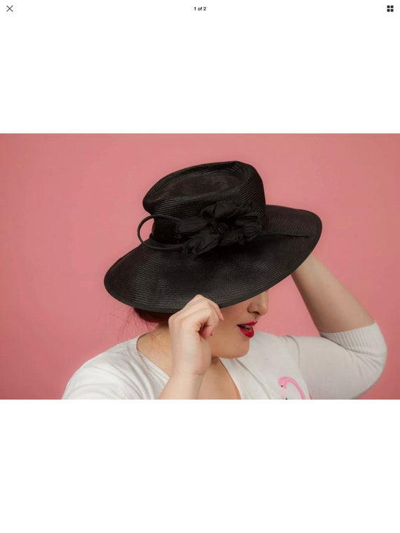 Black formal hat with a flower by Whiteley