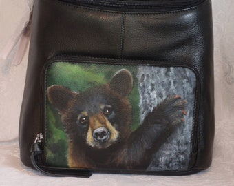 Leather Top Flat Zippered Backpack with a hand painted portrait Shenan, a black bear cub.