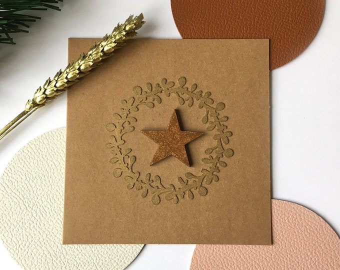 Cardboard greeting card in double kraft - Merry Christmas and Happy New Year - Green Christmas wreath cuts and glittery gilded wood stars