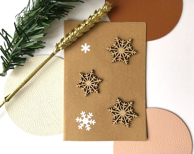 Merry Christmas and Happy New Year greeting card - Double card decorated with wooden and white paper cut flakes on kraft background