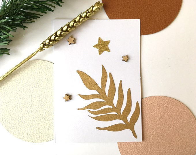 Merry Christmas and Happy New Year greeting card consisting of gold leaf cuts, glittery stars and wood on a white background
