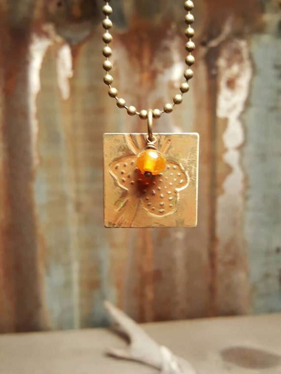 Embossed Brass Pendent with Amber Glass Bead