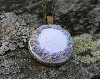 Embroidered necklace pendant with a wreath