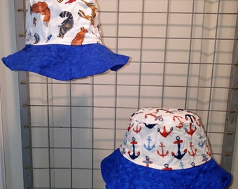"Reversible bucket hats sizes 17"" to 20"" Red white and blue anchors and forest animals with a bright blue brim"