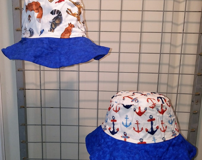 """Reversible bucket hats sizes 17"""" to 20"""" Red white and blue anchors and forest animals with a bright blue brim"""