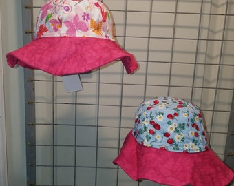 Reversible Sun Hat with Blue fabric with strawberries and flowers and butterflies brim is hot pink
