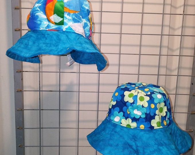 Reversible Sun Hat with Beach balls and Retro Daisy prints Brim is dark aqua