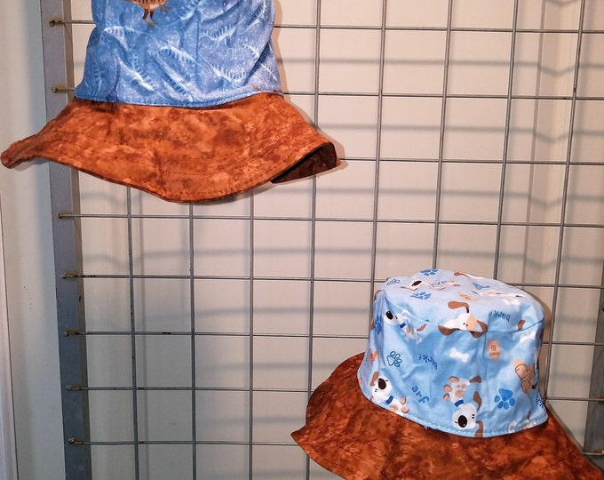 """Reversible bucket hats sizes 17"""" to 20"""" blue dinosaur with either monster truck or dog print with brown brim"""