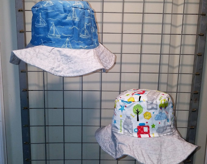 """Reversible bucket hats sizes 17"""" to 20"""" Light blue with sketched sailboats and buildings and cars with a gray brim"""