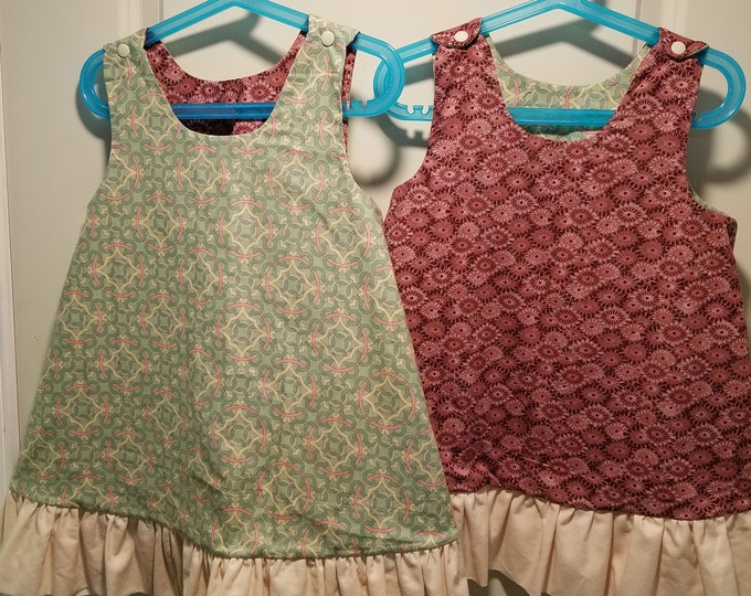 Reversible in Toddler and Kids sizes pink sunburst and tan, pink and green geometric pattern with tan ruffle