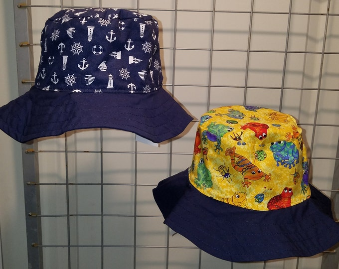 "Reversible bucket hats sizes 15"" to 24"" Navy Nautical with either tropical frogs or airplanes"