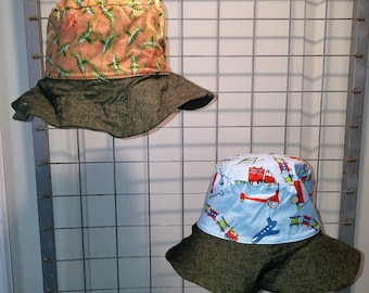 """Reversible bucket hats sizes 15"""" to 20"""" tan dinosaur with toys print and dark green brim"""