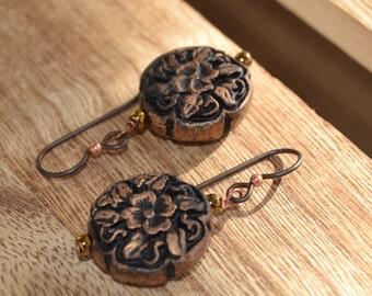 Antiqued black floral cinnabar earrings on niobium ear wires.