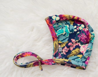 bold floral pilot hat by Little Lapsi. Baby hat with ties.