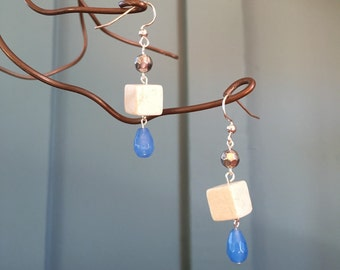 """The """"Building Blox"""" earring: a short pillar of blue glass tear drop shaped bead, sandstone white cube and silver colored facetted bead"""