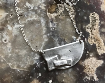 "The ""Adrian"" necklace of a half circle with three rectangles layered up on the necklace pendant"