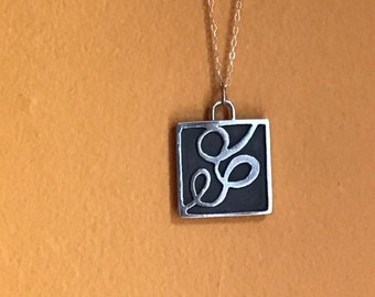 "The ""Eloise"" charm free formed swirling shapes accented with a dark background with a 20inch sterling silver chain"