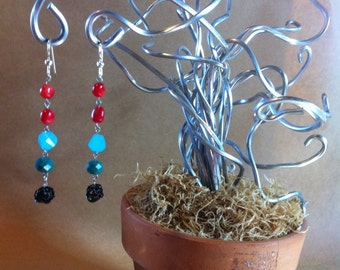 "The ""Building Blox"" earring: a long pillar of red, blue, teal beads an ended with a hand formed wire ball made of black wire"