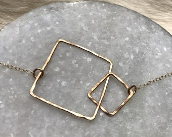 """The 20"""" long Lydia necklace is made of two 14k gold fill interlocking similarly sized squares connected to a chain"""