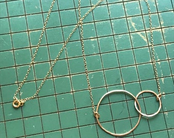 """The 20"""" Lydia necklace is made of two 14k gold fill interlocking circles of contrasting size connected to a gold fill chain"""