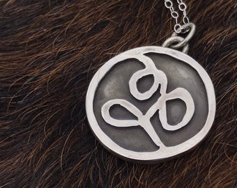 """The """"Eloise"""" charm free formed swirling shapes accented with a dark background in a circle pendant, small size 18 inch silver chain"""