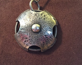 "The ""Joan"" necklace pendant is handmade of sterlinng silver is domed, textured, and antiqued"