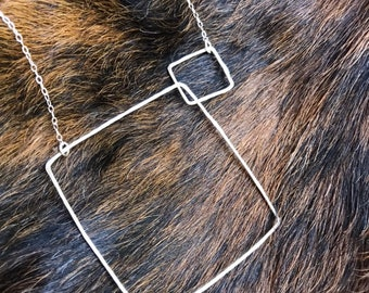 """The 24"""" long Lydia necklace is made of two sterling silver interlocking squares of contrasting size connected to a sterling sliver chain"""