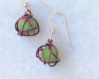 Leesa earring: bright green glass bead with purple colored wire and sterling silver earwire
