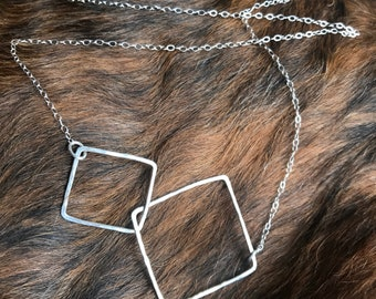 "The 23"" long Lydia necklace is made of two sterling silver interlocking squares of contrasting size connected to a sterling sliver chain"