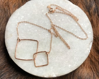 "The Lydia necklace is two interlocking 14k rose gold circles of contrasting size with plated rose gold chain, 18"" long"