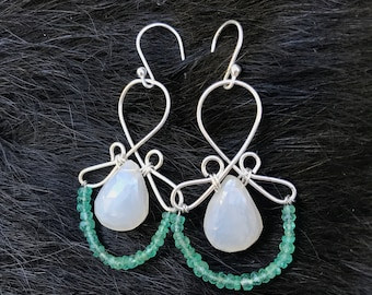 The Emma earring: hand formed sterling silver wire with a white chalcedony teardrop bead and a string of natural bright green emeralds