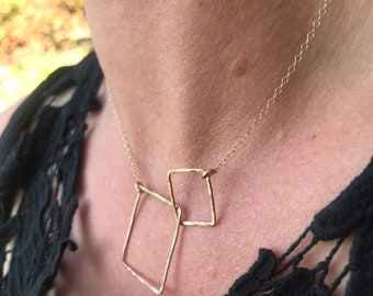 """The 18"""" long Lydia necklace is made of two 14k gold fill interlocking squares of contrasting size connected to a gold fill chain"""