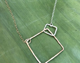"""The 18"""" Lydia necklace is made of a 14k gold fill and a sterling silver interlocking squares of contrasting size on gold and silver chain"""