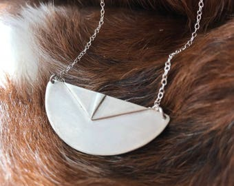 "The ""Adrian"" necklace of a half circle with two triangles layered up on the necklace pendant"