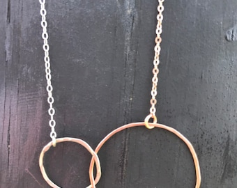 The Lydia necklace is two interlocking circles, one small silver and one big 14k rose gold with 20 inch silver chain