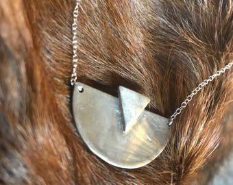 """The """"Adrian"""" necklace of a half circle with one triangle layered on the necklace pendant"""