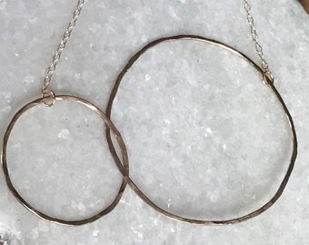 The 21 inch long Lydia necklace is made of two gold fill interlocking circles of contrasting size connected to a gold fill chain