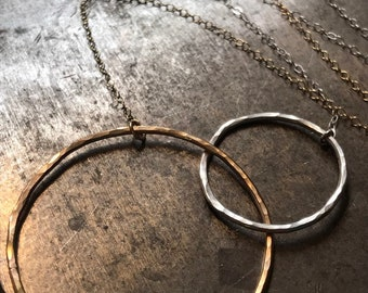 The Lydia necklace is one large 14k gold fill one small silver interlocking circle with half a sterling sliver half gold chain, 19 inch long