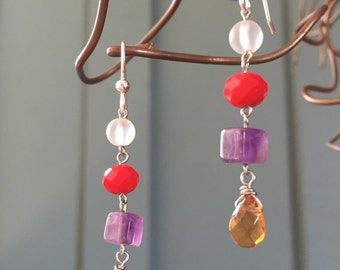 """The """"Building Blox""""earring: mustard yellow teardrop glass bead, amethyst cube, red faceted acrylic bead, frosted clear bead and silver hooks"""