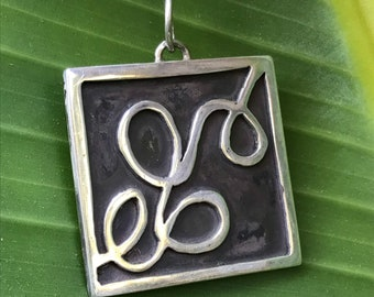 """The """"Eloise"""" charm free formed swirling shapes accented with a dark background in a square pendant"""