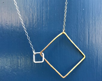 """The 20"""" Lydia necklace is made of a 14k gold fill and a sterling silver interlocking squares of contrasting size on gold and silver chain"""