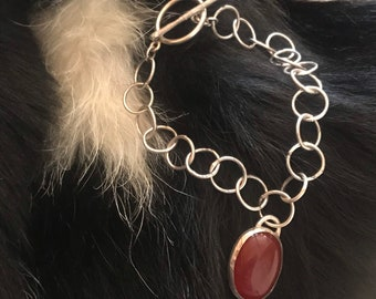 Alicia bracelet 7 1/4 inch length, 3/8 inch circle link handmade sterling silver metal with toggle clasp closure and handset carnelian charm