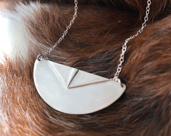 """The """"Adrian"""" necklace of a half circle with two triangles layered up on the necklace pendant"""