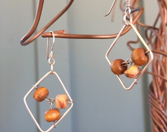 """The """"Jewel-ia"""" earring: wooden and jasper beads attached in the center of a sterling silver diamond shaped frame"""